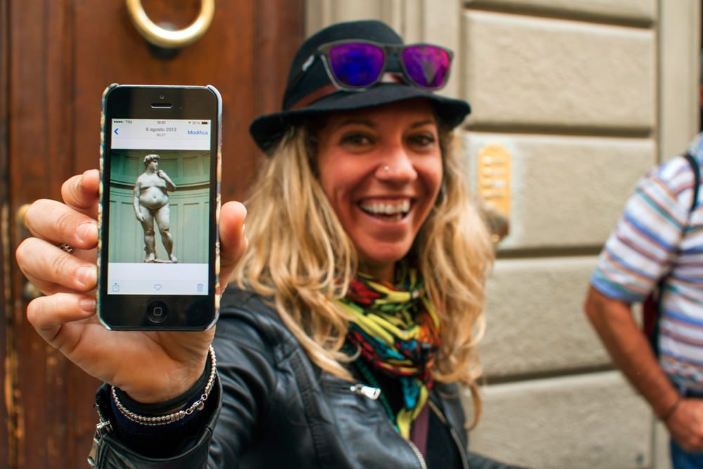 A Walks of Itay guide poses with her camera-phone-picture of Michelangelo's David.