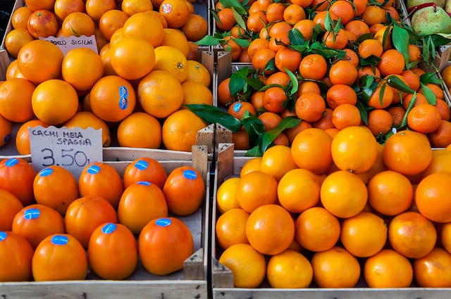 The Campo dei Fiori in Rome hosts an open-air food market that offers delicious food year round, like these persimmons and oranges in January! Photo by Marco Verch (flickr)